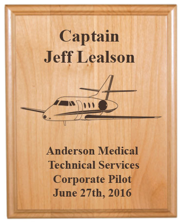 Personalized alder wood plaque with custom engraved jet design and text.