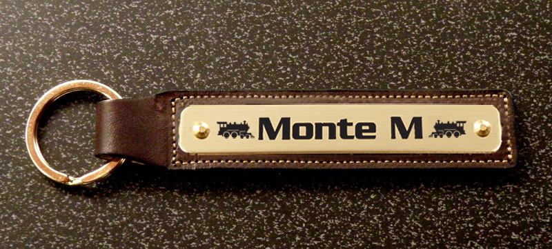 Personalized train design leather nameplate key fob with engraved text and train design.